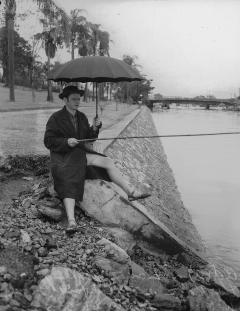 StateLibQld_1_105748_Adrian_Zana_fishing_in_the_rain_at_Breakfast_Creek,_1952